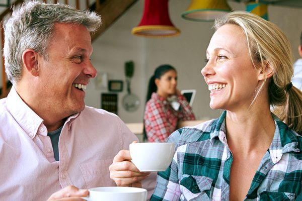 "A man and woman in a coffee shop, sitting down and looking at each other while smiling and ""cheers""-ing their coffee mugs"