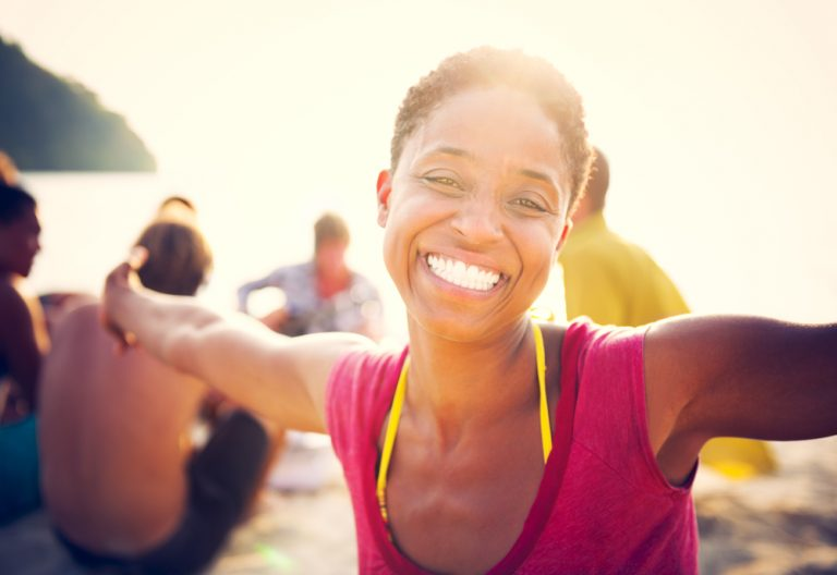 young woman with short hair spreads her arms in happiness and smiles while on the beach with friends